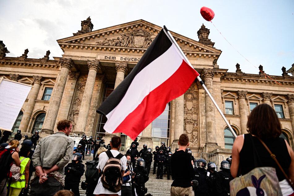 Teilnehmer einer Kundgebung gegen die Corona-Maßnahmen stehen vor dem Reichstag, ein Teilnehmer hält eine Reichsflagge.