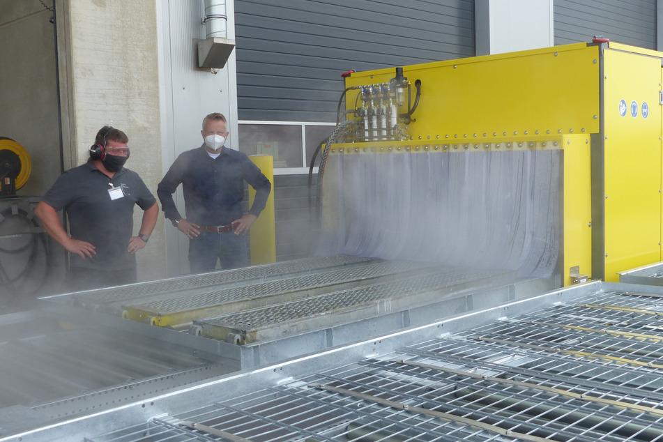 """Matthias Schultenkemper (l.) von der Hersteller-Firma aus Oelde und """"Gemeinhardt Gerüstbau""""-Chef Dirk Eckart schauen sich die neue Waschanlage an."""