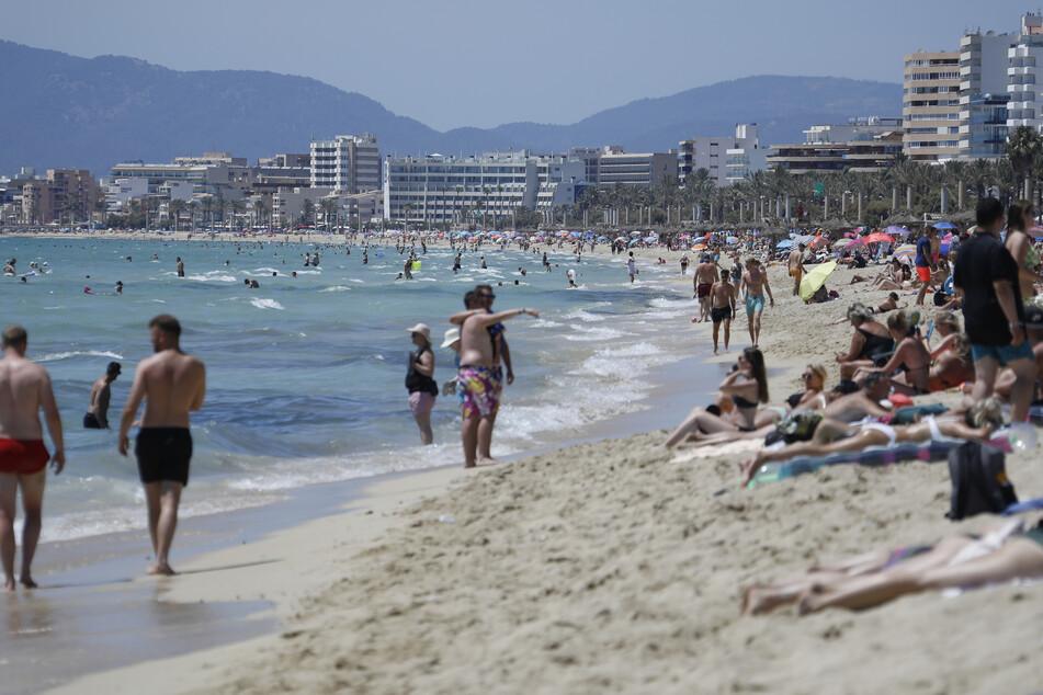 Touristen am Strand von Arenal in Palma de Mallorca.
