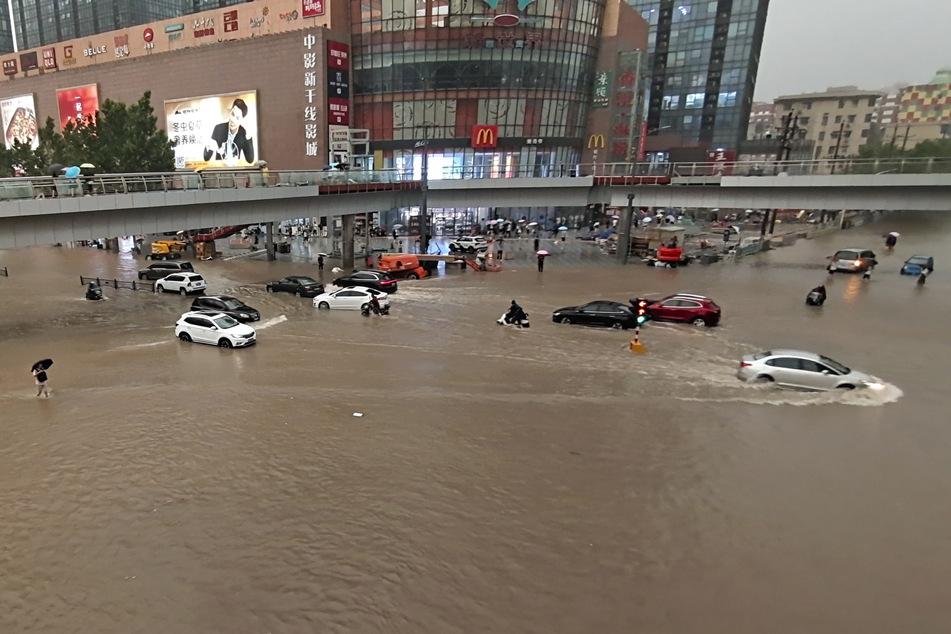 Fahrzeuge stehen in der zentralchinesischen Provinz Henan auf einer überfluteten Straße.