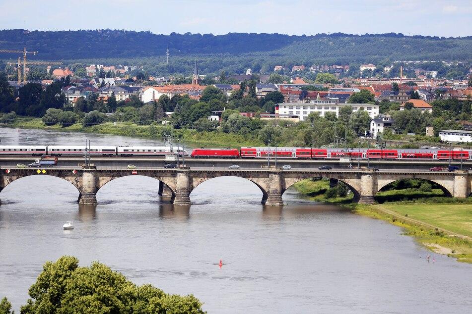Ein Regionalzug und ein ICE überqueren die Marienbrücke in Dresden.