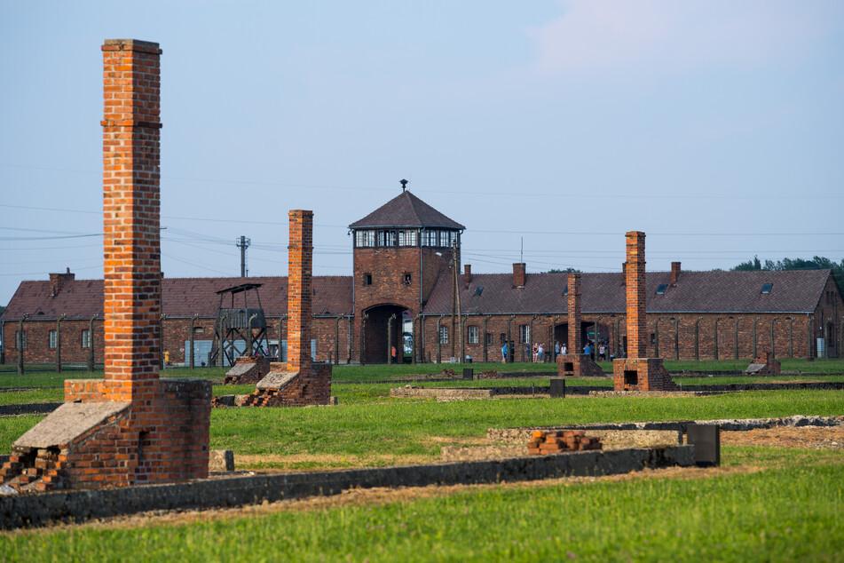 Blick auf das historische Tor (Innenseite) und die Schornsteine der Baracken im früheren Vernichtungsslager Auschwitz-Birkenau.