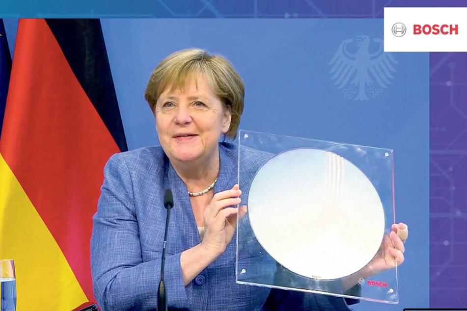 Bundeskanzlerin Angela Merkel (66, CDU) hält einen 300-Millimeter-Wafer. Auf diesen Siliziumscheiben werden die Mikro-Chips produziert.
