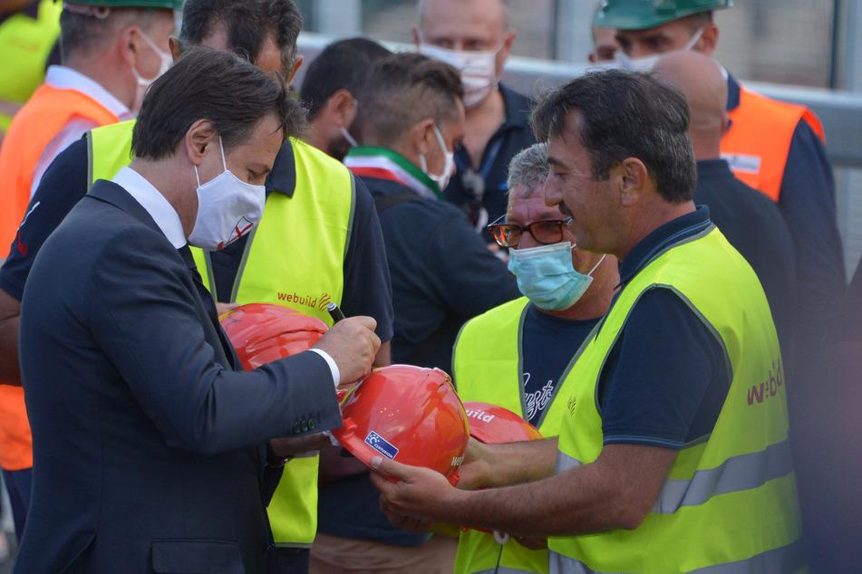 Genua: Giuseppe Conte (l), Ministerpräsident von Italien, unterschreibt den Helm eines Bauarbeiters während der Einweihungsfeier der Brücke San Giorgio. (Archivbild)