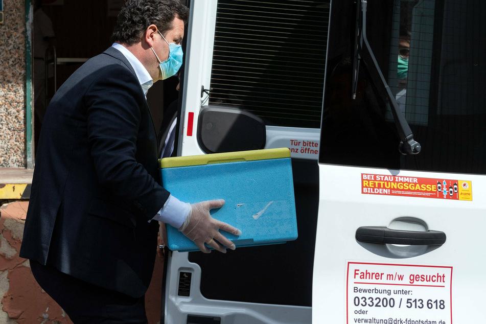 Hubertus Heil (47, SPD) nimmt aus einem Transporter eine Kiste mit Essen heraus.