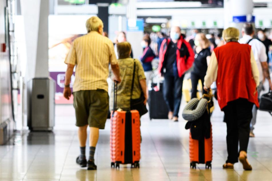 Reisende gehen Anfang Juli am Flughafen Frankfurt mit Gepäck durch die Abflughalle im Terminal 1.
