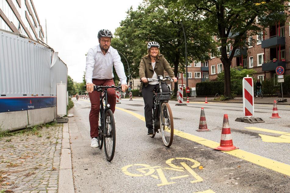 Anjes Tjarks (39, Bündnis90/Die Grünen), Hamburgs Senator für Verkehr und Mobilitätswende und Kirsten Pfaue, Koordinatorin für Mobilitätswende in der Behörde für Verkehr und Mobilitätswende (BMV) fahren im Stadtteil Rothenbaum auf einer Pop-Up-Bikelane Fahrrad.
