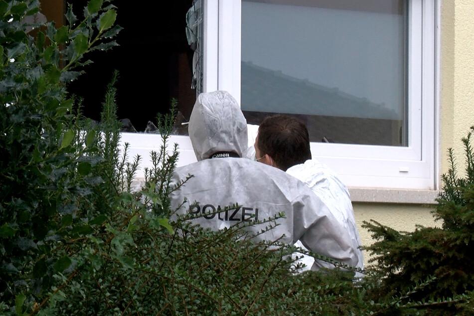 Beamte der Spurensicherung stehen vor einer eingeschlagenen Fensterscheibe im Erdgeschoss. Der 23-Jährige drang auf diesem Weg erneut in die Wohnung ein.