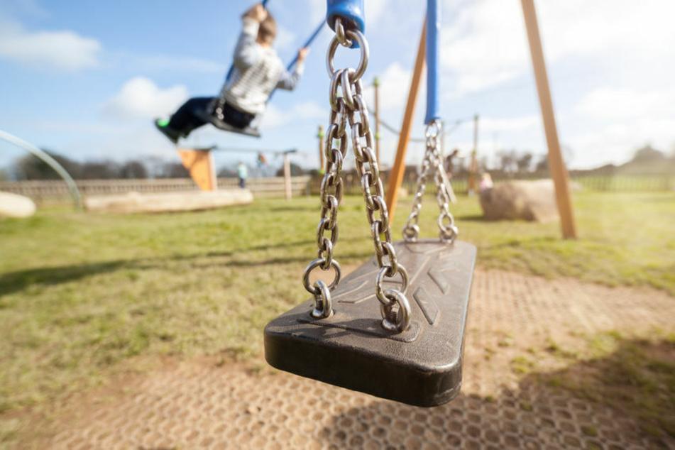 Eine leere Spielplatz-Schaukel mit Kindern im Hintergrund. (Symbolfoto)
