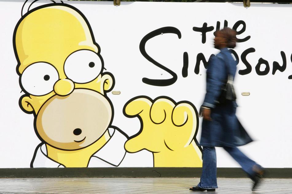 """Eine Frau geht in Brüssel an einem Werbeplakat für den Kinofilm """"The Simpsons"""" vorbei. (Archivbild)"""