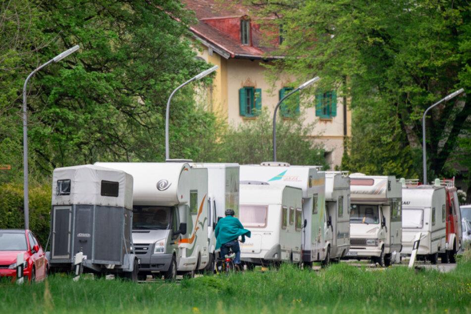 Ein Radfahrer fährt in einer Münchner Straße an geparkten Anhängern, Wohnmobilen und Wohnwagen vorbei.