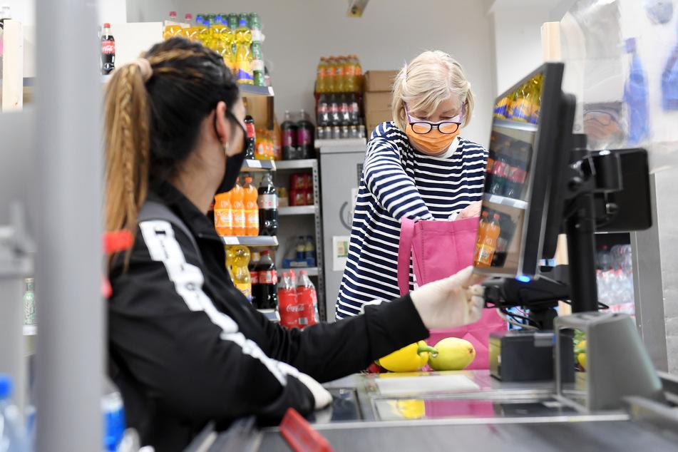 Eine Kundin verpackt in einem Lebensmittelgeschäft ihre Einkäufe an der Kasse und trägt eine Maske als Mund- und Nasenschutz.
