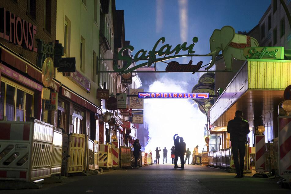 """Passanten gehen am Ende einer Protestaktion von Kiez-Gastronomen, Club- und Kneipenbesitzer durch die Straße """"Große Freiheit"""" auf der Reeperbahn."""