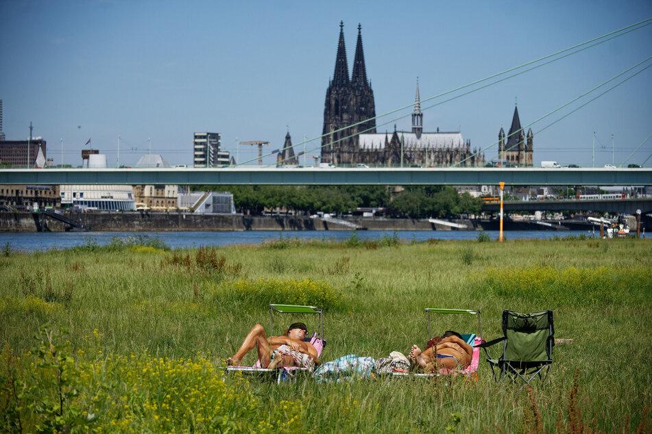 Zwei Männer genießen am Rheinufer in Köln die Sonne. Die Temperaturen klettern zur Wochenmitte bis auf 29 Grad.