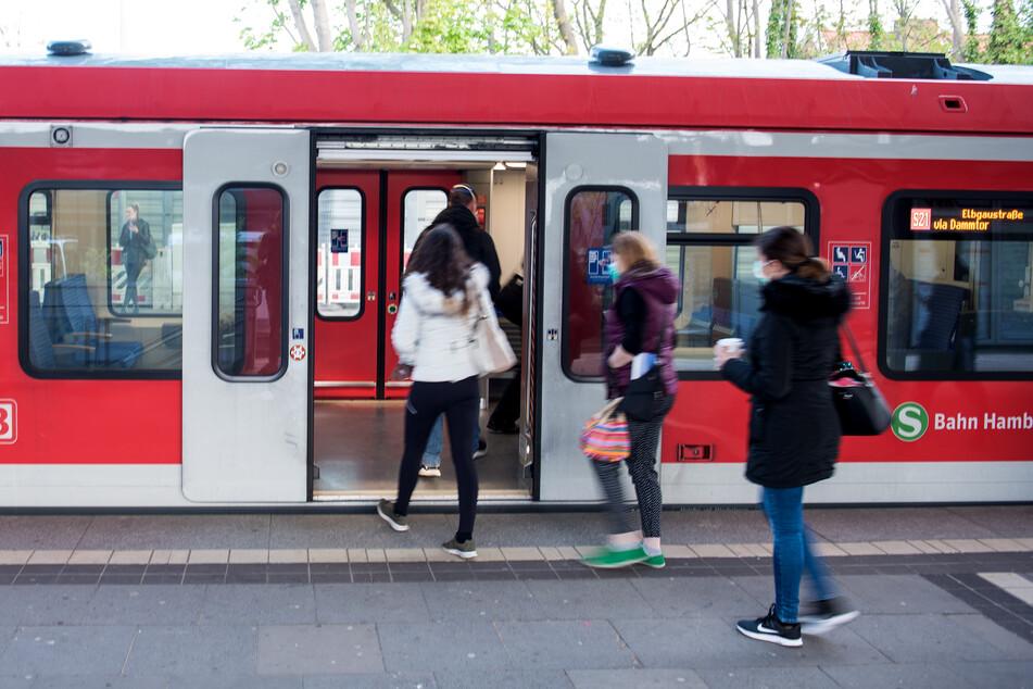 Fahrgäste mit einem Mund-Nasen-Schutz steigen an einem Bahnhof in eine S-Bahn ein.