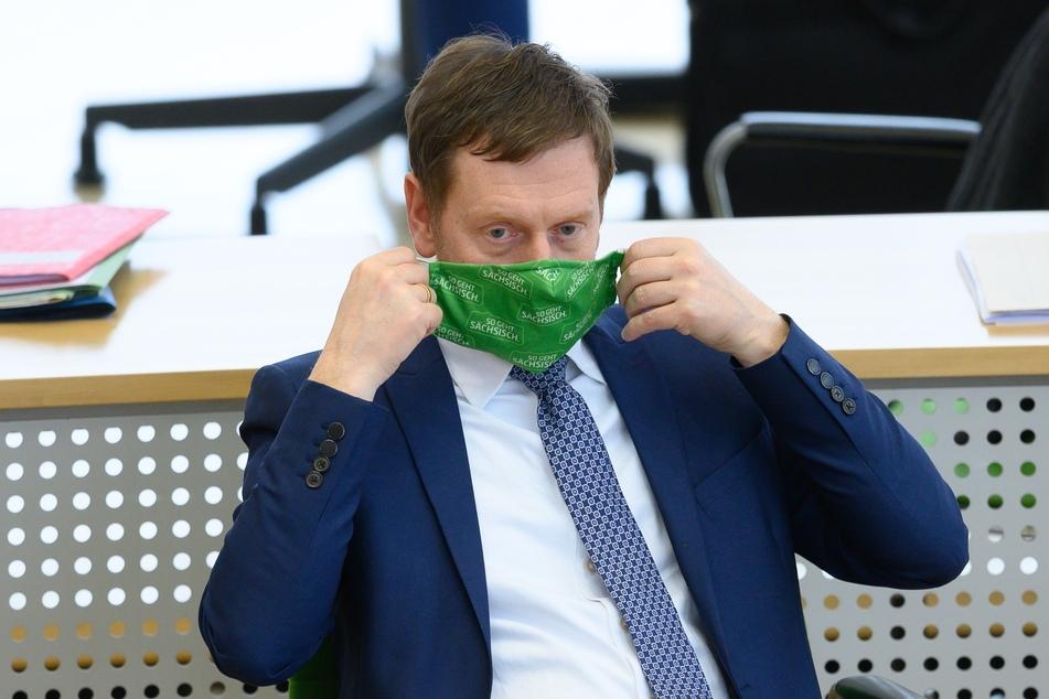 Michael Kretschmer (CDU), Ministerpräsident von Sachsen, hält im Plenum einen Mund-Nasen-Schutz bei der Landtagssitzung.
