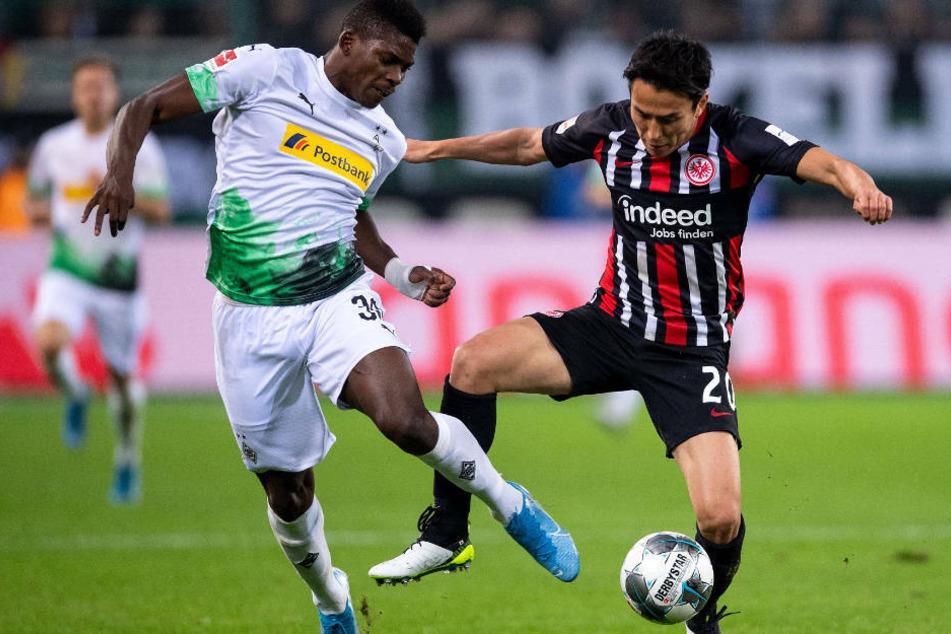 Gladbachs Breel Embolo (l) und Frankfurts Makoto Hasebe kämpfen um den Ball: Die geplante Revanche für die Hinspiel-Niederlage (2:4) gegen Borussia Mönchengladbach am Sonntag wird ohne Publikum ausgetragen.