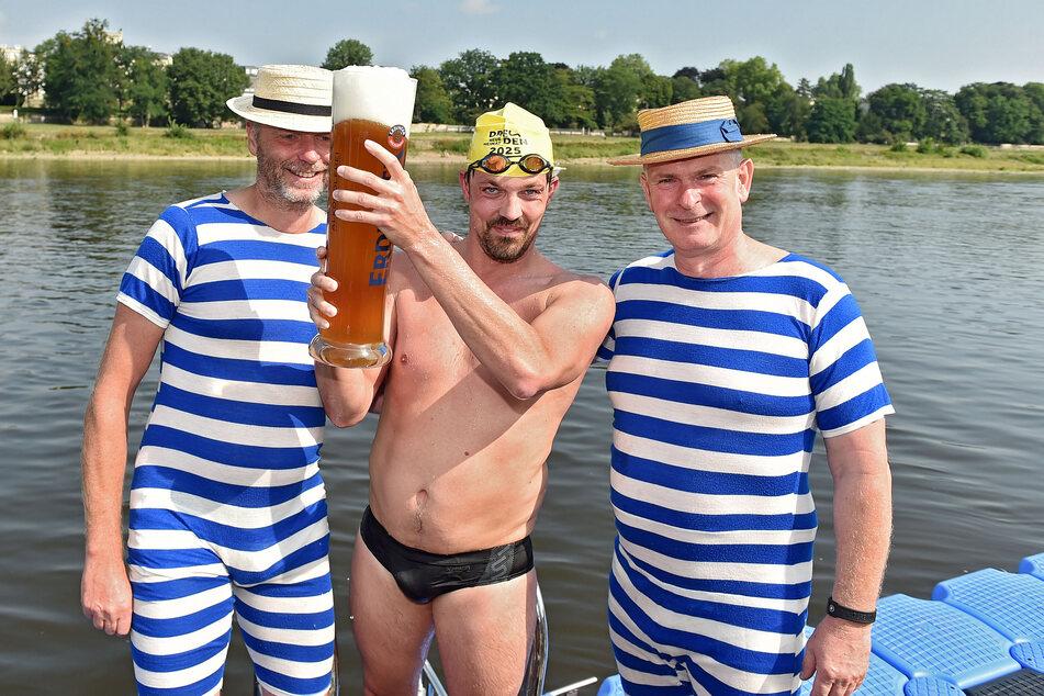 Holte beim letzten Elbeschwimmen 2019 den Sieg: Andreas Suck (34) aus Leipzig. Fährgarten-Wirt Jens Bauermeister (56, r.) gratuliert im zünftig-gestreiften Badeanzug.