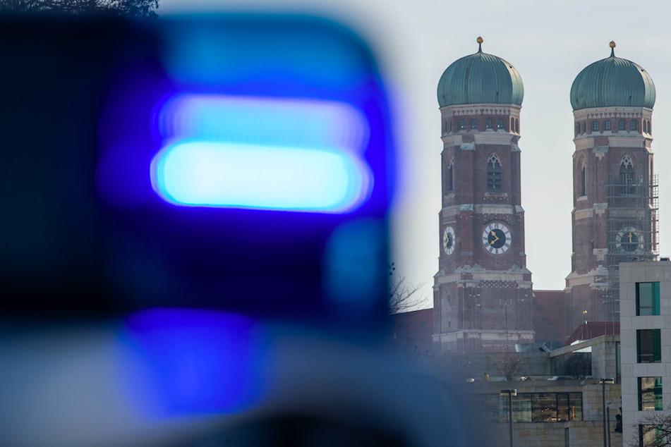Ein Blaulicht einer Polizeistreife ist vor den Türmen der Frauenkirche zu sehen. (Symbolbild)