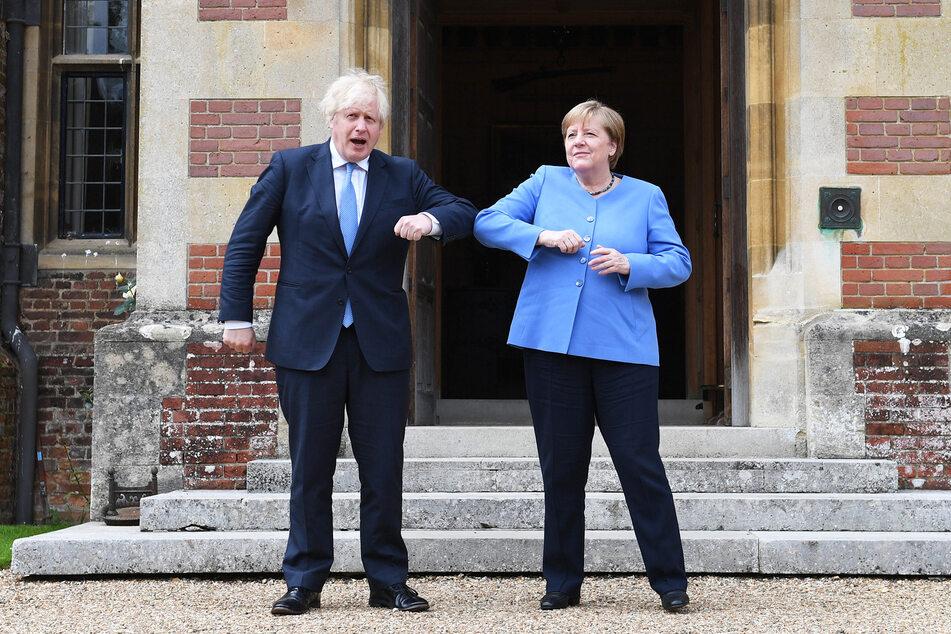 Ellenbogen an Ellenbogen grinsen Boris Johnson (57) und Angela Merkel (66, CDU) in die Kameras.