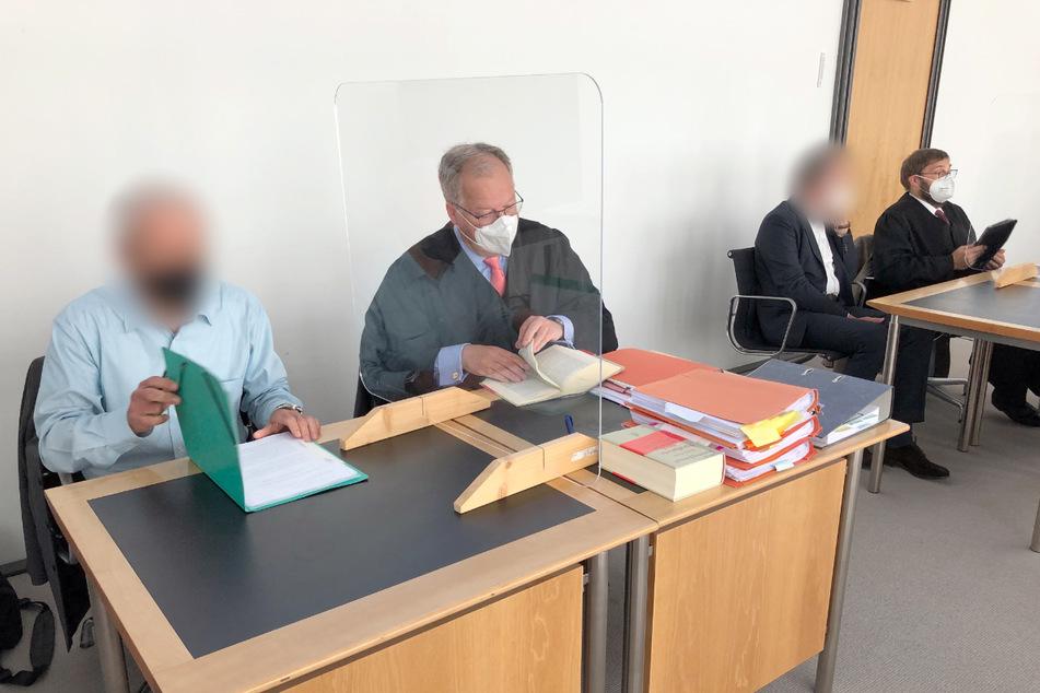 Die Angeklagten (1.v.l. sowie 3.v.l.) sitzen mit ihren Verteidigern vor dem Start der Verhandlung im Gerichtssaal des Amtsgerichts.
