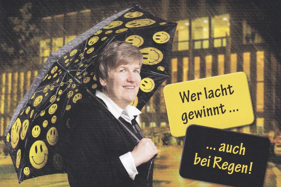 Ein humorvolles Foto: Carmen Goglin (55) nutzt jede Gelegenheit um ihr Lachen in die Welt zu tragen. Hier mit einem Smiley-Regenschirm vor der Reutlinger Stadthalle.
