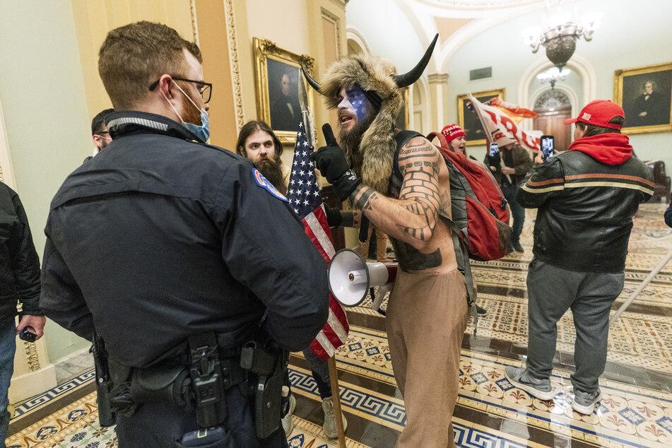 """Jacob C. und andere Unterstützer von US-Präsident Trump stehen auf dem Gang vor der Senatskammer im US-Kapitol und diskutieren mit einem Polizisten des Kapitols. Unter den Eindringlingen sind auch Anhänger der rechten """"QAnon""""-Verschwörungstheorie gewesen."""
