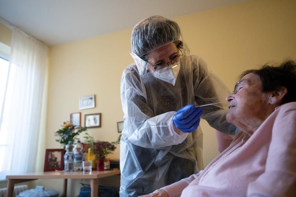 Eine Altenpflegerin führt im einen Antigen-Corona-Schnelltest durch.