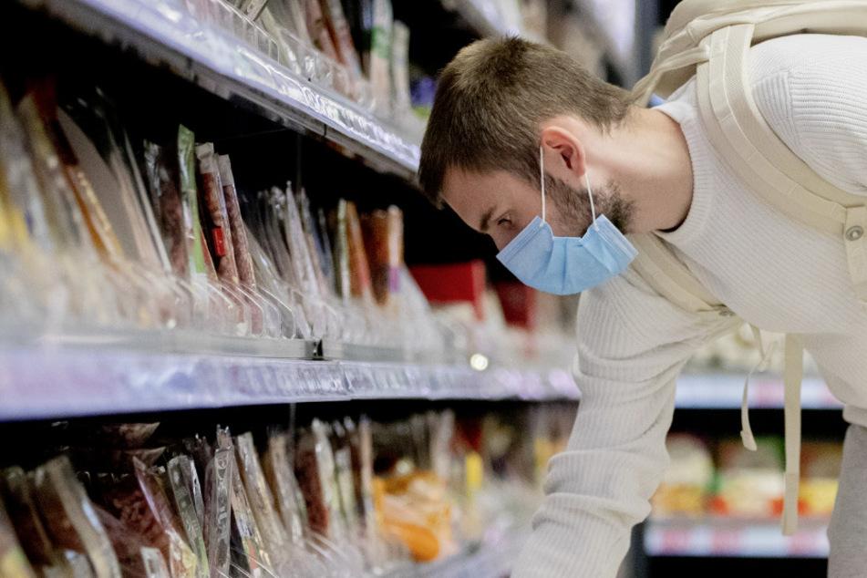 Ein Mann trägt beim Einkauf eine Schutzmaske. (Archivbild)