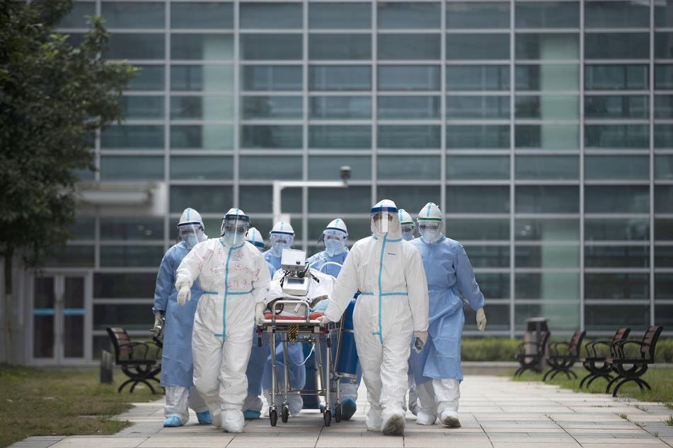 Medizinisches Personal in Schutzkleidung transportiert einen COVID-19-Patienten in den CT-Raum eines Krankenhauses.