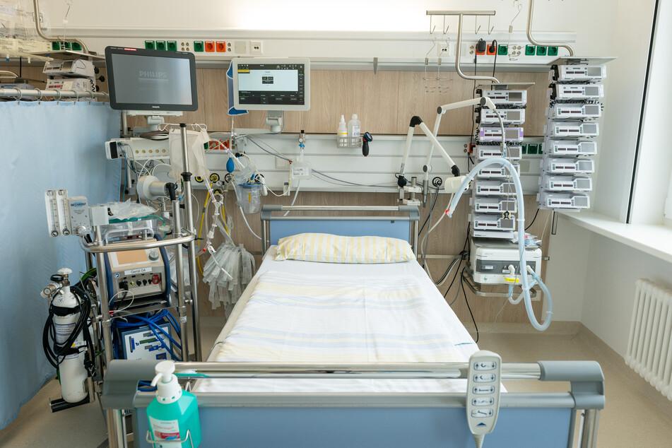 Ein Intensivbett auf einer Intensivstation der Uniklinik Dresden. Links neben dem Bett steht eine Herz-Lungen-Maschine, oben befinden sich die Überwachungsmonitore für die Vitalfunktionen. Rechts neben dem Bett steht ein Beatmungsgerät und Infusionstechnik.