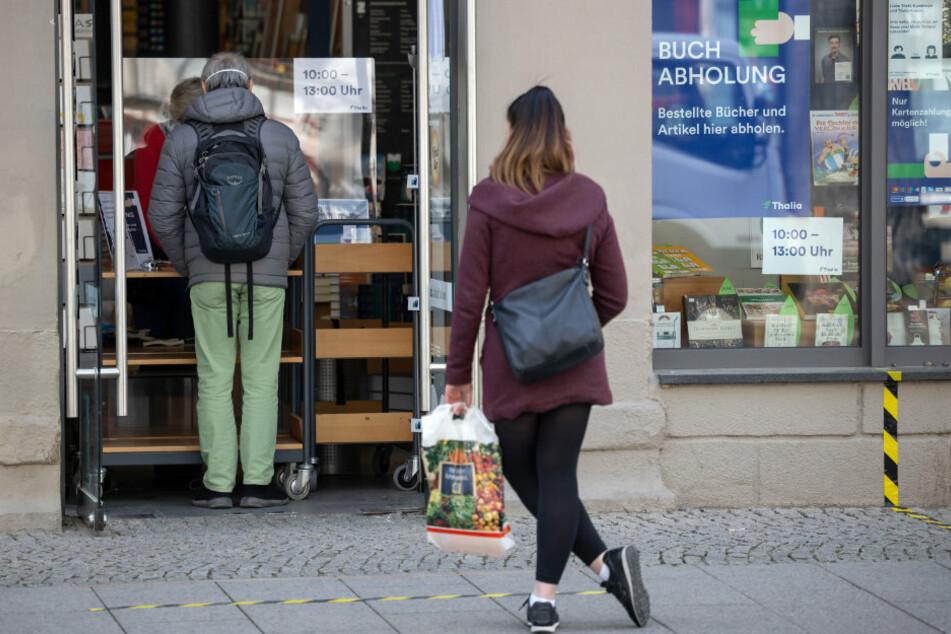 In Weimar warten Menschen vor einer Buchhandlung, um sich vorbestellte Bücher an der Ladentür abzuholen.
