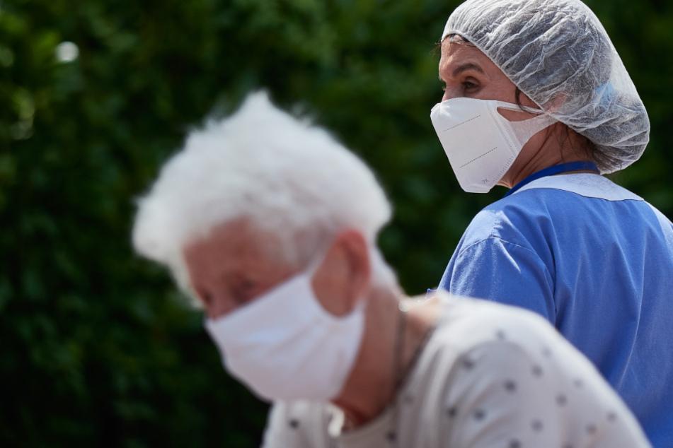 Eine Arbeiterin steht hinter einer Bewohnerin, die in sicherem Abstand mit ihren Familienangehörigen am Eingang eines Pflegeheims spricht.