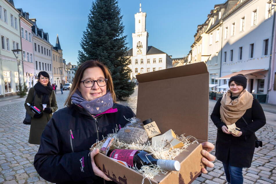 """Mandy Illing (37) präsentiert die """"Weihnachtsmarkt@Home""""-Box mit Isabell Kosmitzki (42, l.) von Katl & Bell und Mandy Fiebig (43) von Naturella auf dem Schneeberger Marktplatz."""
