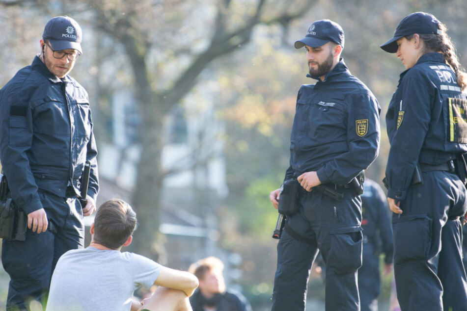 Polizisten sprechen Menschen in einem Park an. (Symbolbild)