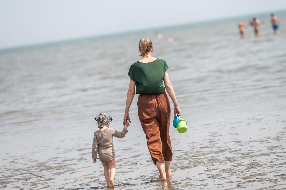 Eine Strandbesucherin ist bei sommerlichen Temperaturen mit ihrer Tochter am Nordseestrand von Schillig.
