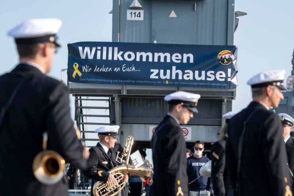 """Mit Musik und Willkommensbanner wird die einlaufende """"Berlin"""" in Wilhelmshaven begrüßt."""