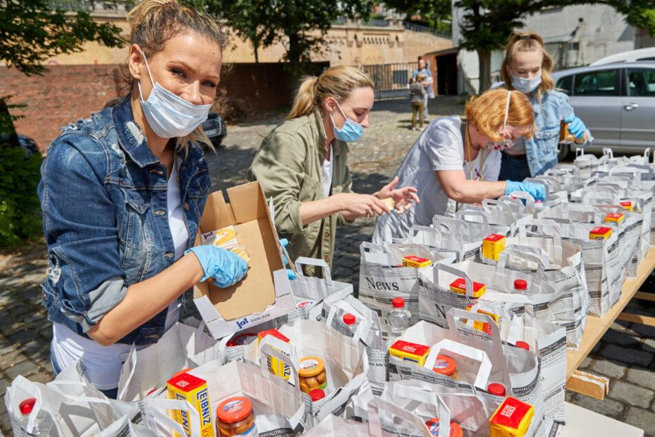 Yasmina Filali (v. l. n. r.) packt zusammen mit den freiwilligen Helferinnen Jeannine Postel, Tina Schenderlein und Sam Kennedy Essenstüten für Obdachlose.