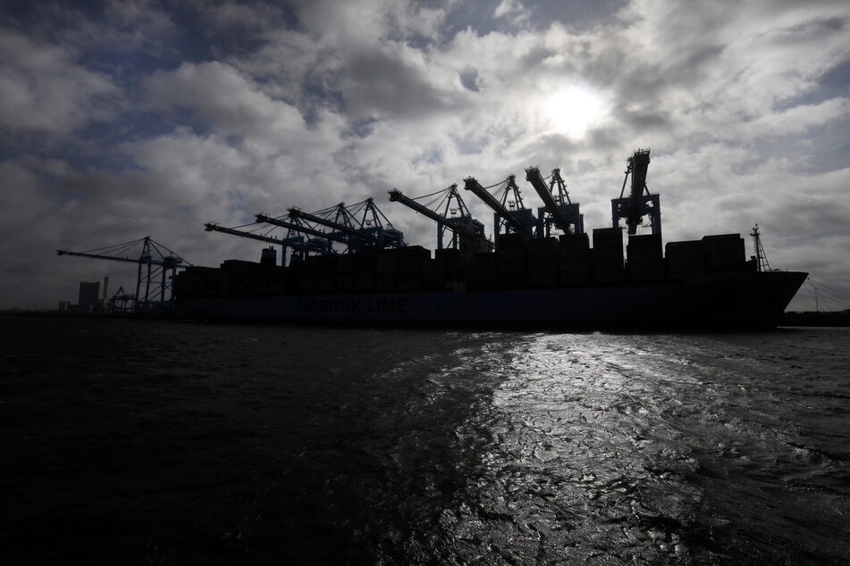 A container ship's silhouette with the sun in the port of Rotterdam.