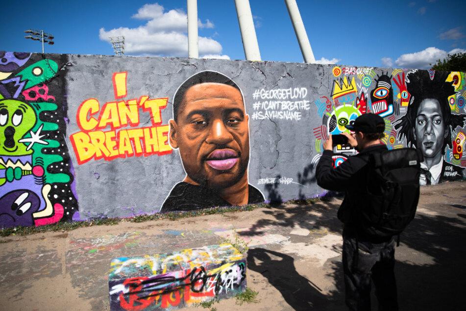 """Berlin: Ein Mann fotografiert ein Graffiti des Künstlers """"EME Freethinker"""" im Mauerpark, welches George Floyd zeigt"""