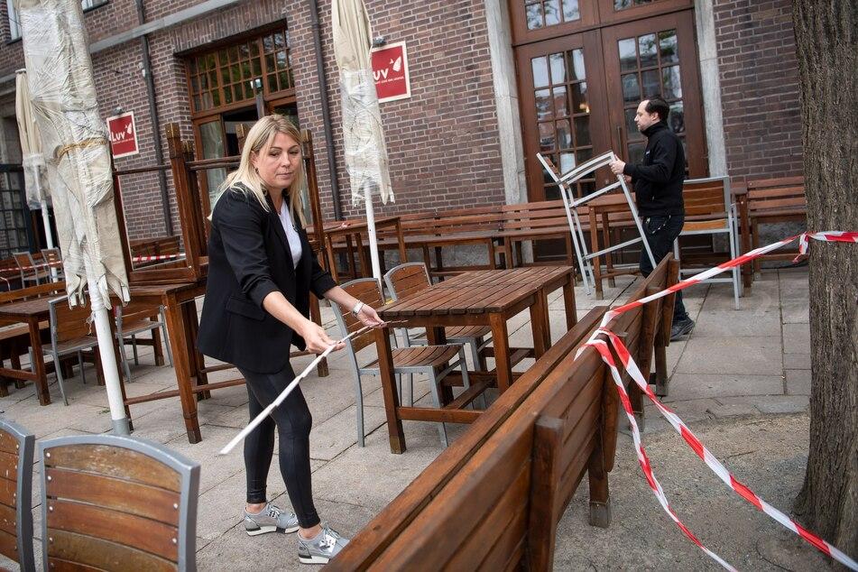 Vor der Wiedereröffnung des Bremer Restaurants werden mit einem Zollstock die Abstände zwischen Tischen und Stühlen vermessen.