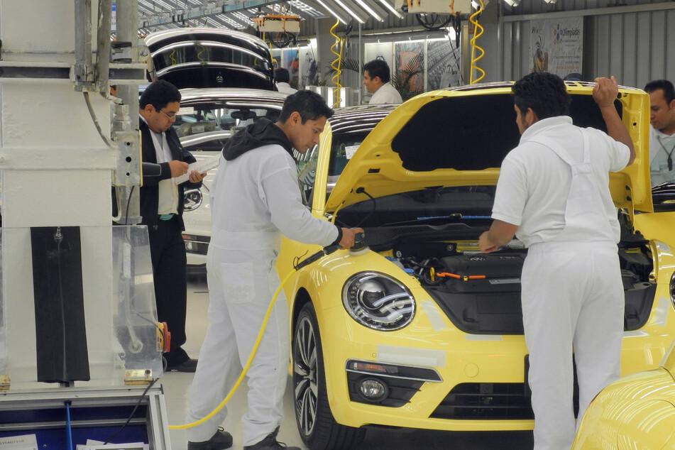 Mitarbeiter eines VW-Werks montieren am einen Beetle. (Archivbild)