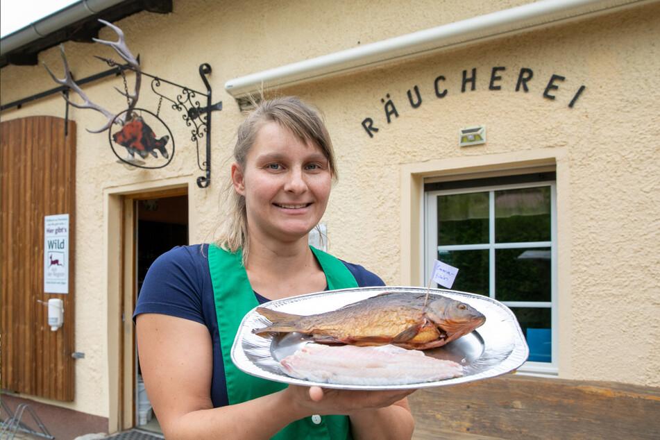 Mitarbeiterin Linda Bradler (30) vor dem Hofladen: Die Kreuzung aus Schuppenkarpfen und Karausche ist ein hervorragender Speisefisch.