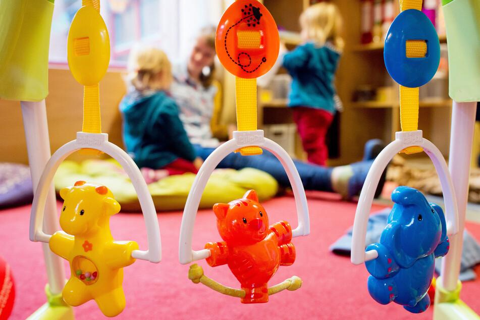Kinder spielen in einer Kita. Wenn sie von Eltern abgeholt werden müssen, wird es für diese bald teuer.