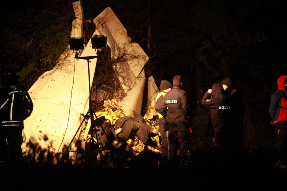 Einsatzkräfte stehen neben dem zerschellten Flugzeug.