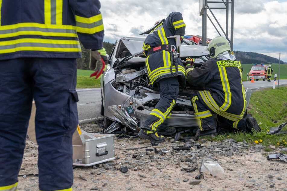 Einsatzkräfte der Feuerwehr hantieren an dem kaputten Ford.