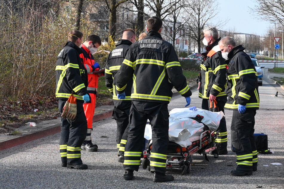 Feuerwehrleute stehen um die Trage mit dem toten Motorradfahrer. Er starb noch an der Unfallstelle.