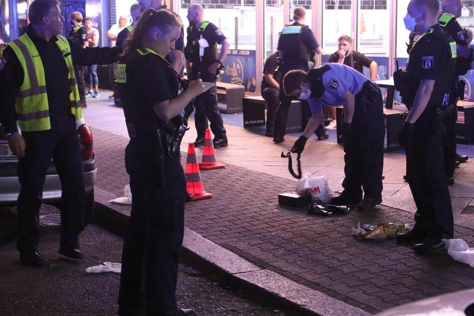 Polizisten einer Einsatzhundertschaft suchen den Tatort auf der Sonnenallee in Berlin-Neukölln ab.