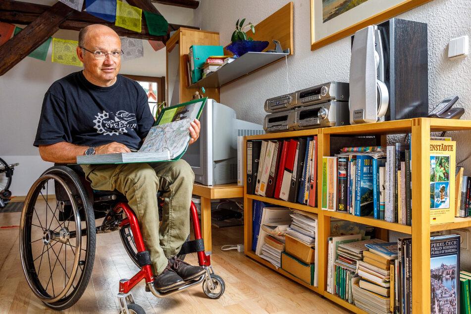 """Veit Riffer in seinem Wohnzimmer über den Dächern von Pirna. Er fährt mit seinem Handbike gern """"lange Kanten"""" und hat so auch schon viele Alpenpässe bezwungen."""