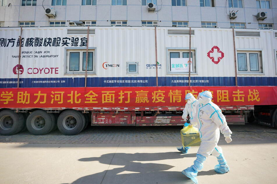 Delivery people pick up and transport patient samples for the Wuhan Leishenshan Hospital.